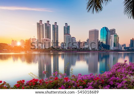 A Beautiful Benchakitti Park near the skyscraper business district,View Bangkok city with park at sunset with reflection of skyline,Thailand