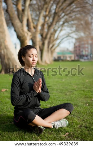 A beautiful black woman doing yoga meditation outdoor in a park - stock photo