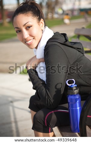 A beautiful black woman sitting on a park bench after exercise - stock photo