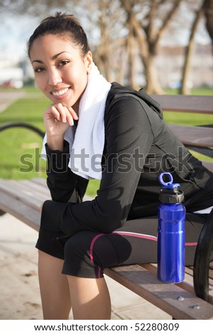 A beautiful black woman sitting on a park bench after exercise