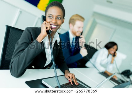 A beautiful, black, young woman working at a call center in an office with her red haired partner on the other end of the desk talking to another customer - stock photo
