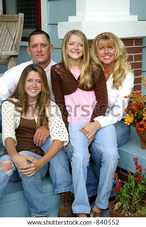 A beautiful blond family sitting together on their front porch. - stock photo