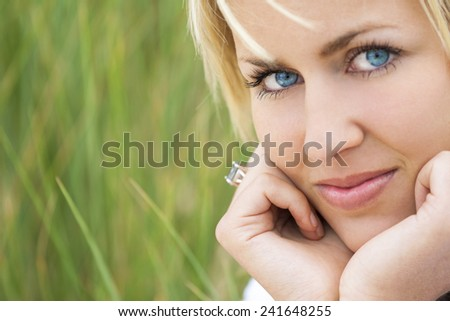 A beautiful blond model with blue eyes against a natural green grass background - stock photo