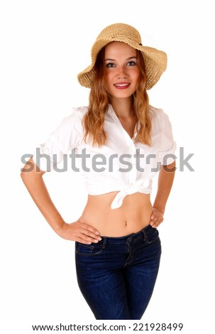 A beautiful blond woman in a white blouse and blue jeans, wearing a  straw hat, standing isolated for white background.  - stock photo