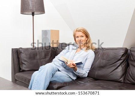 A beautiful blond woman is sitting on a couch reading a book