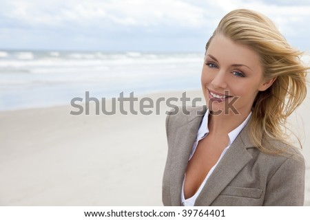 A beautiful blond young woman at the beach illuminated by natural light with her hair blowing in the wind - stock photo