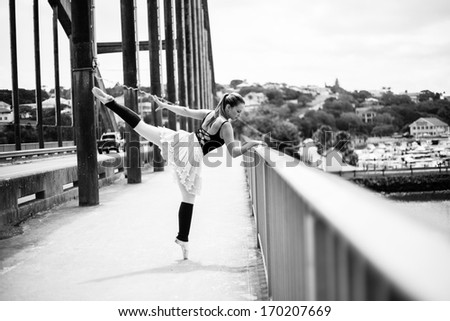 A beautiful blonde ballerina is giving a kick whilst leaning against the bridge railing over the river. - stock photo