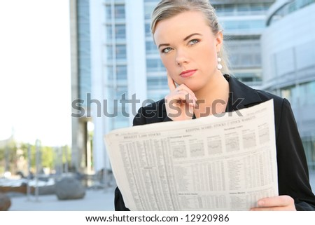 A beautiful blonde business woman in front of office building reading newspaper