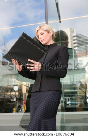 A beautiful blonde business woman looking at binder - stock photo