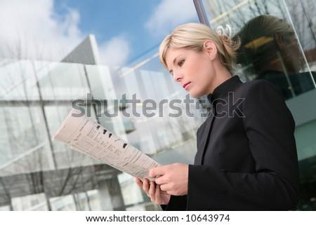 A beautiful blonde business woman reading newspaper - stock photo