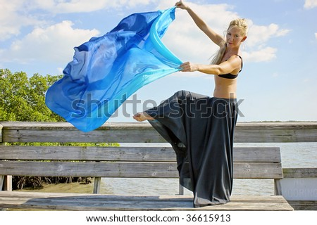a beautiful blonde dancer making looking at viewer with her arms and one leg raised , her long veil blowing in the breeze as she balances on one foot - stock photo