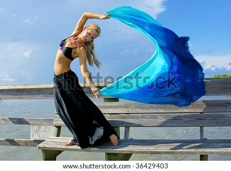a beautiful blonde fit and trim belly dancer strikes a dramatic pose as the wind blows he hair, skirt, and veil - stock photo
