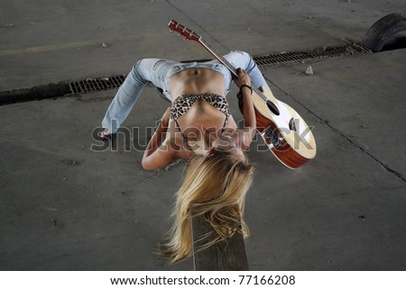 A beautiful blonde in a long-abandoned, dilapidated warehouse lying on a makeshift wooden bench with her acoustic guitar.  She's wearing tattered jeans with a leopard-print bikini top.  High angle. - stock photo