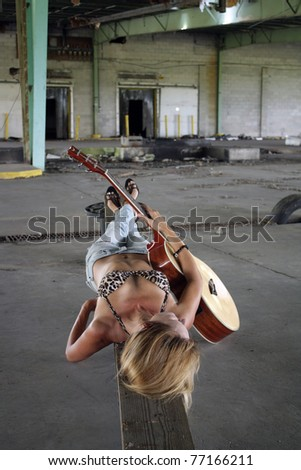 A beautiful blonde in a long-abandoned, dilapidated warehouse lying on a makeshift wooden bench with her acoustic guitar.  She's wearing tattered jeans with a leopard-print bikini top. - stock photo