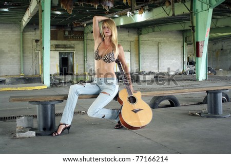 A beautiful blonde in a long-abandoned, dilapidated warehouse sits with her acoustic guitar on a makeshift wooden bench.  She's wearing tattered jeans with a leopard-print bikini top. - stock photo