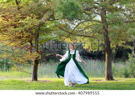 A  beautiful blonde lady wearing a long green medieval gown, wandering in a forest.
