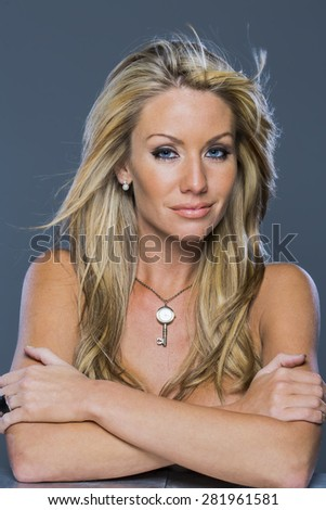 A beautiful blonde model posing in a studio environment - stock photo