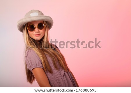 A beautiful blonde teenage girl wearing sunglasses in studio, she also has a hat on her head. - stock photo