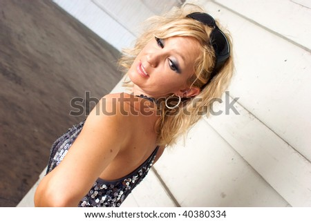 A beautiful blonde woman is looking back at a long mark on her shoulder. - stock photo