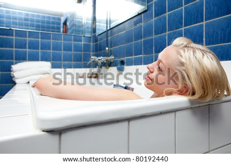 A beautiful blonde woman relaxing in a spa bath - stock photo