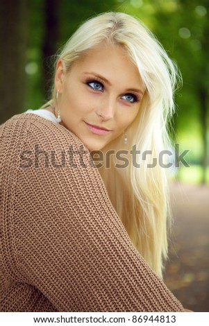A beautiful blue-eyed young blonde woman gazes intently in to the distance in a park, close up face. - stock photo