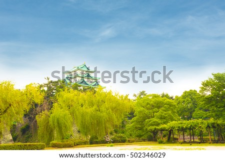 A beautiful blue sky day above Nagoya Castle stronghold over a green treeline in Japan