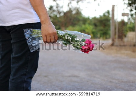 A beautiful bouquet of red roses is held by hand of middle aged woman. Valentine's day or romance date concept