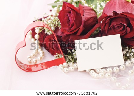A beautiful bouquet of red roses with red heart, pearls, and gift tag with copy space on pink tulle background - stock photo