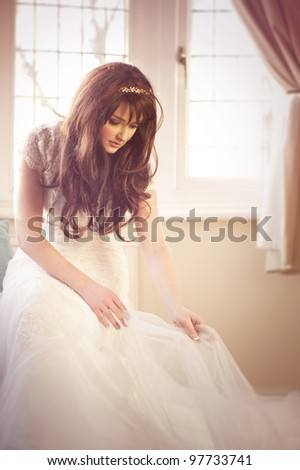A beautiful bride adjusting her wedding dress. - stock photo