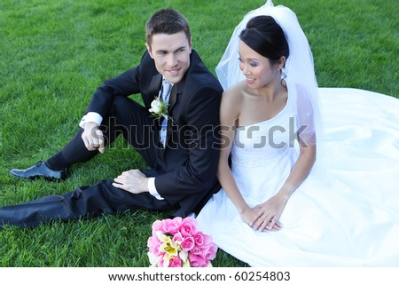 A beautiful bride and handsome groom on grass during wedding - stock photo