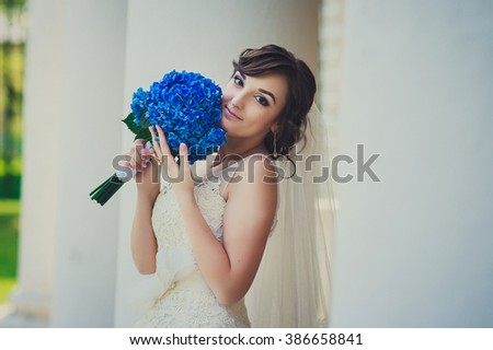 a beautiful bride is standing near the white stone columns in the city park, bride is wearing gorgeous white wedding dress and holding a bouquet of bright blue flowers