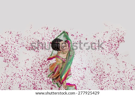 A beautiful bride showered with rose petals - stock photo