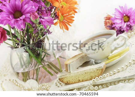 A beautiful bright ladies tea party with cup of tea, lemon biscotti and fresh flowers, copy space - stock photo
