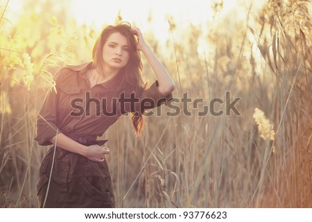 A beautiful brunette girl posing in a field on autumn. - stock photo