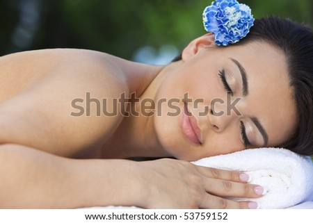 A beautiful brunette Hispanic Latina woman relaxing outside on a massage table at a health spa with a blue flower in her hair