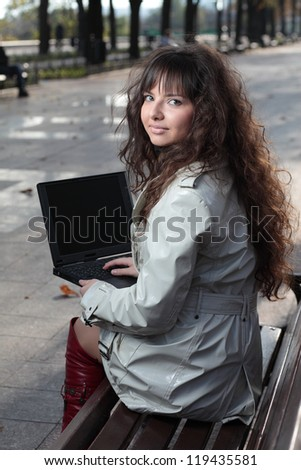 A beautiful brunette model working on a computer. - stock photo