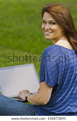 A beautiful brunette model working on a computer and talking on a mobile phone in an outdoor environment