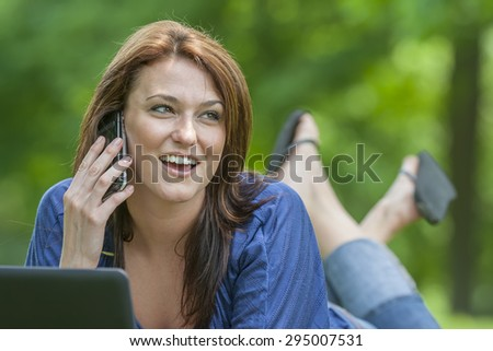 A beautiful brunette model working on a computer and talking on a mobile phone in an outdoor environment - stock photo