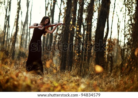 A beautiful brunette woman playing at the violin in the forest.Art photo. - stock photo