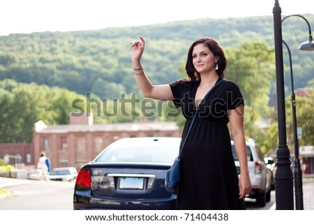 A beautiful brunette woman waving her arm tries to hail a cab at the side of the road in the city. - stock photo
