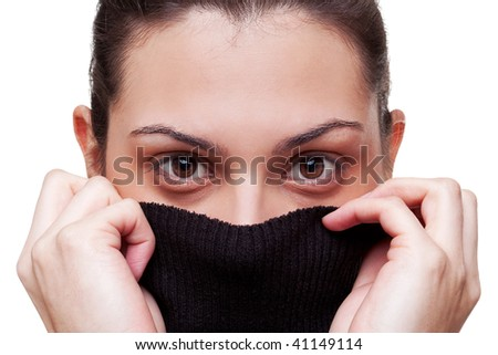 A beautiful brunette woman with big brown eyes pulling her jumper up over her face, white background. - stock photo