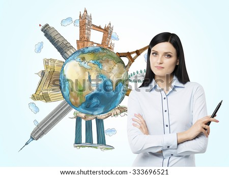 A beautiful brunette woman with mark pen and a globe with sketched famous touristic places in the world. Elements of this image furnished by NASA. - stock photo