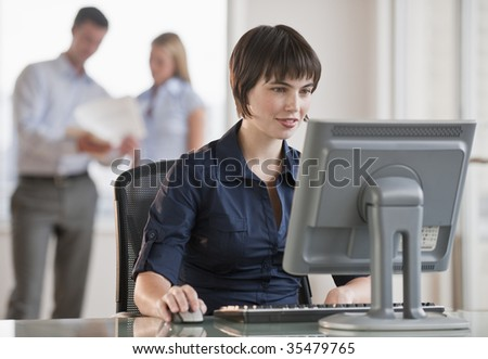 A beautiful brunette working at a computer, while two employees discuss paperwork behind her.  She is smiling. Horizontally framed shot.