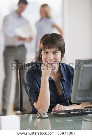 A beautiful brunette working at a computer, while two employees discuss paperwork behind her.  She is smiling. Vertically framed shot. - stock photo
