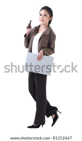A beautiful business woman walking with laptop and on the phone - stock photo