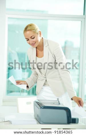 A beautiful businesswoman printing documents in office - stock photo