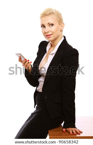 A beautiful businesswoman sitting on a table and using a mobile phone, isolated on white background