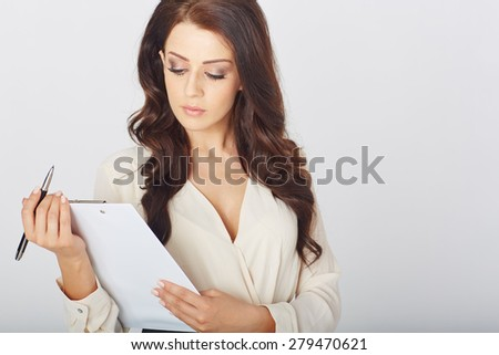 a beautiful businesswoman with a clipboard  in studio
