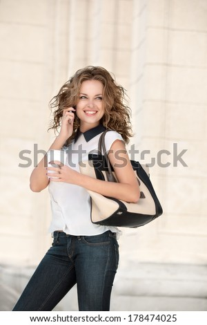 A beautiful businesswoman with the phone holding a cup of take away coffee. - stock photo