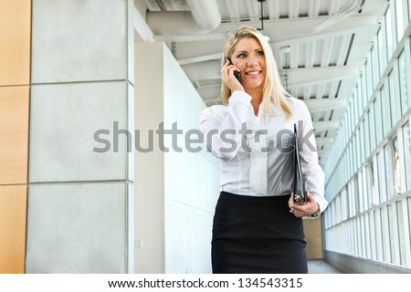 A beautiful businesswomen talking on the phone and walking - stock photo